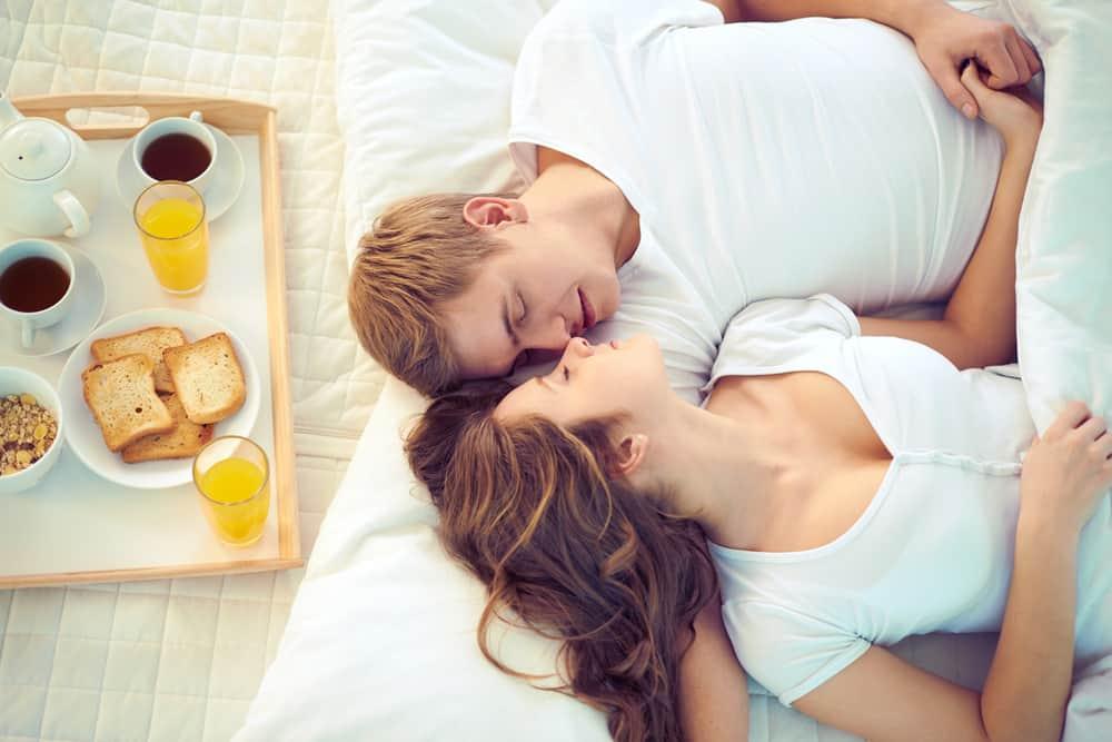unga par som äter frukost i sängen