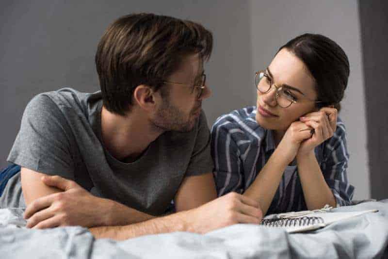 unga par som ligger i sängen och tittar på varandra