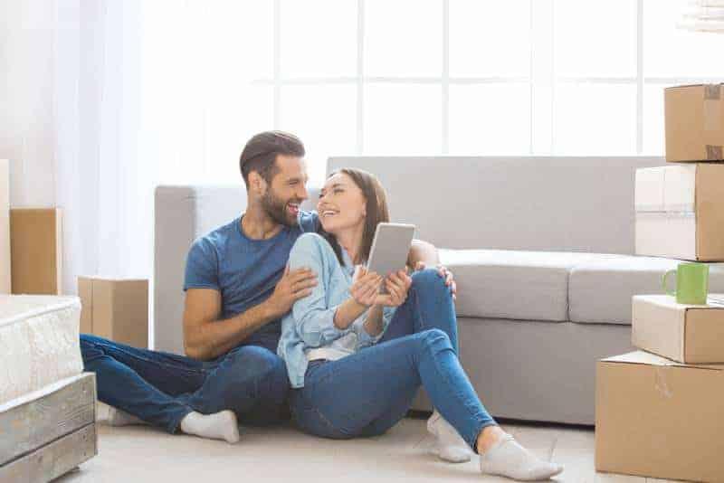 ungt par i kärlek som sitter på golvet hemma och ser varandra