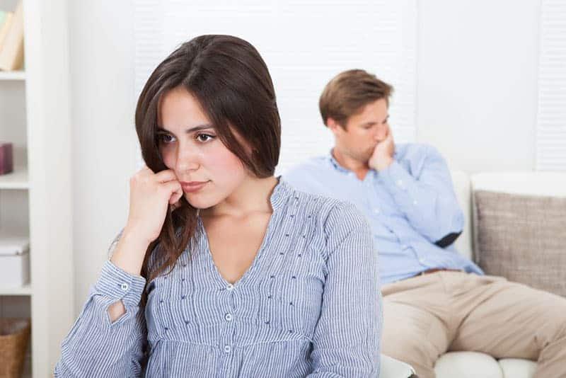 upprörd kvinna med mannen som sitter på soffan