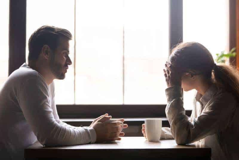 upprörd par pratar på café