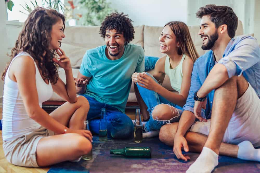 vänner skrattar åt en blyg tjej när de spelar sanning eller vågar