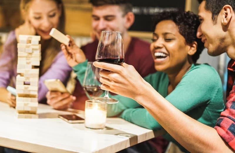 vänner som spelar brädspel och dricker vin hem