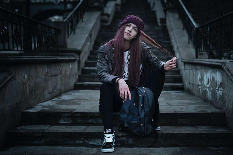 kvinna sitter i steg med ryggsäck