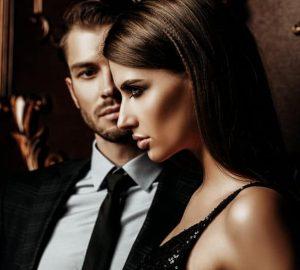 kvinna i svart klänning med mannen i bakgrunden