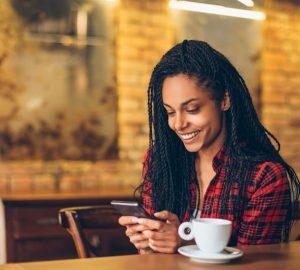 ung kvinna med mobiltelefon på café