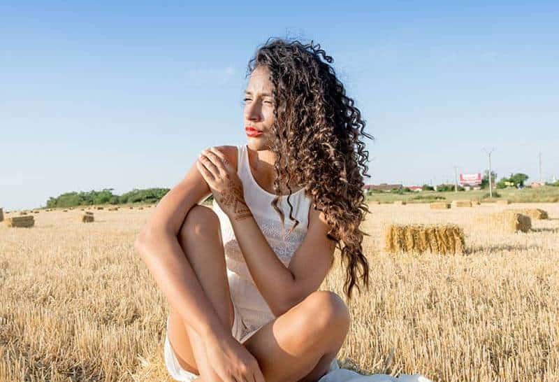 lockigt hår kvinna sitter på brunt fält