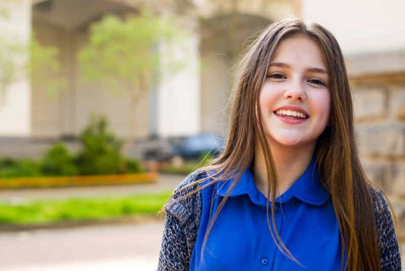 portrait of a smiling girl in a blue T-shirt and sweater