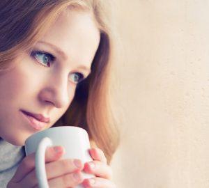 vacker drömmande tjej med en kopp varm dryck kaffe vid fönstret