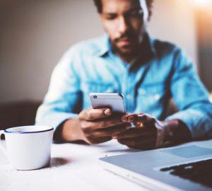 man använder smartphone medan du sitter vid träbordet