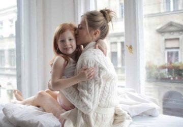 kvinna kysser dotter i sängen