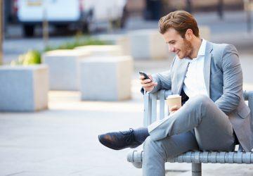 stilig man som sitter och håller sin telefon