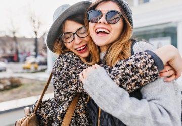 två leende tjejer som kramar utanför