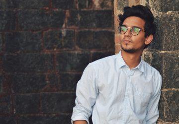 man i vit skjorta med glasögon som står nära väggen