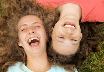 två kvinnor som ligger på gräset och ler