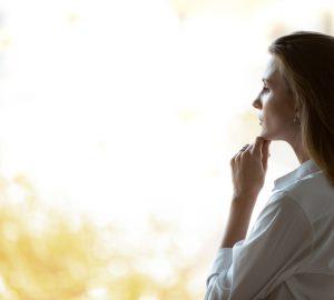 kvinna som tittar genom fönstret