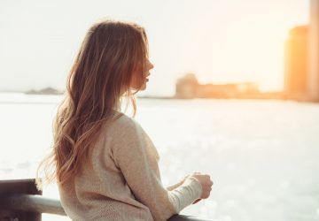 kvinna med långt hår som står ensam utomhus