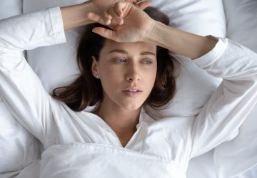 vacker sorglig kvinna som ligger i sängen ensam