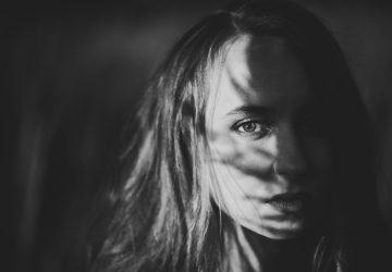 Framsidan av flickan på en bakgrund av skugggräs i höst på naturen