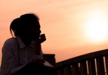 En ledsen kvinna sitter ensam under solnedgången