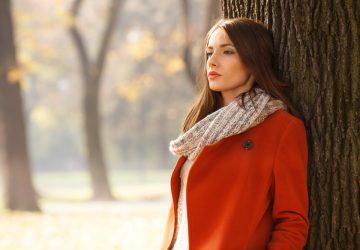 vacker ung fundersam kvinna som står utomhus ensam