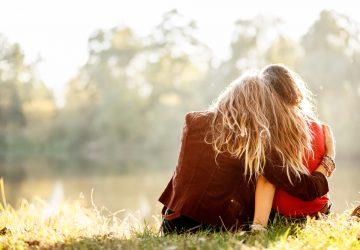 två kvinnor som sitter på gräset och kramar