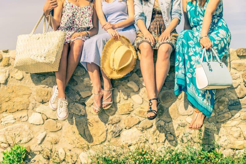 fyra kvinnliga vänner som sitter på väggen utomhus