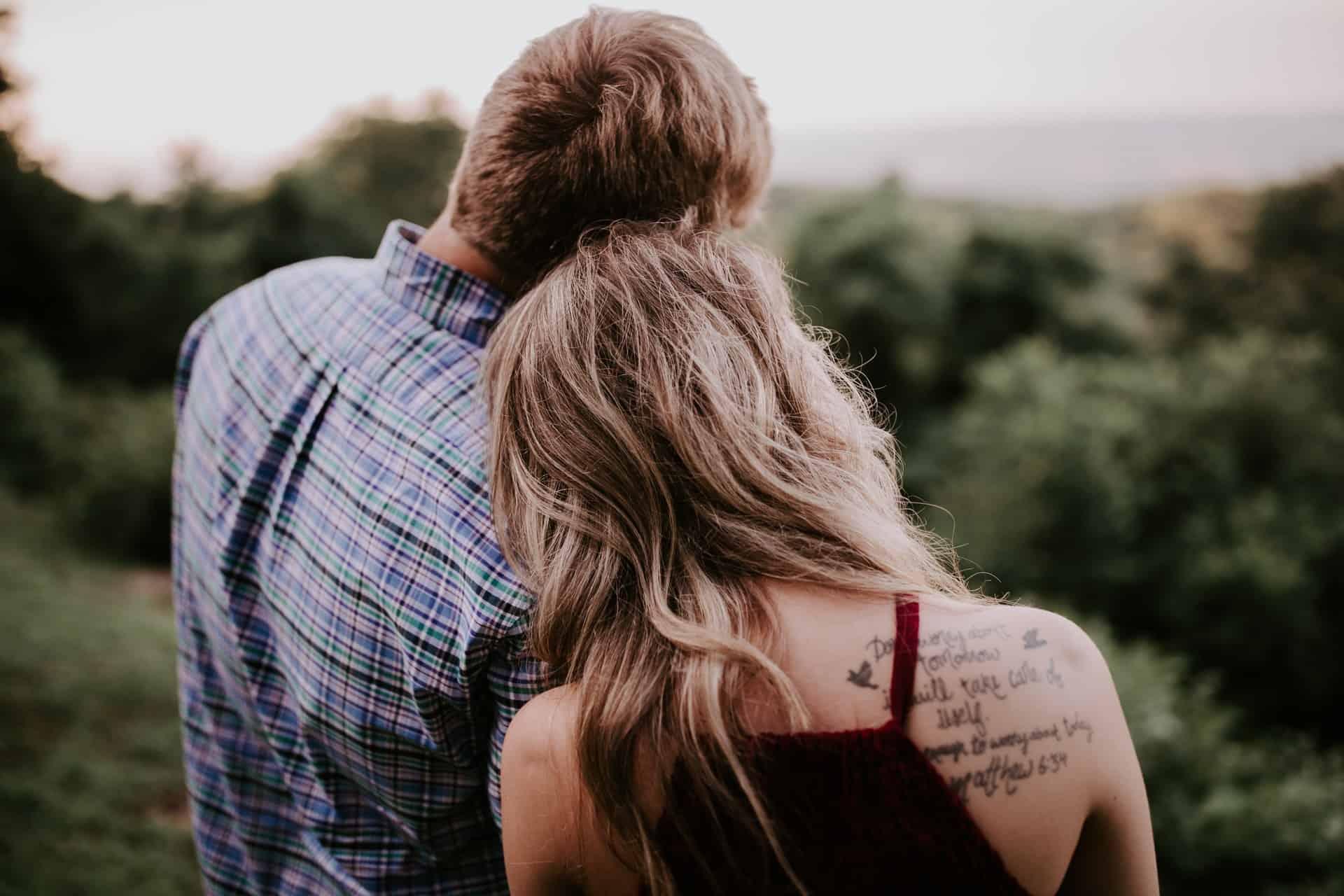 kvinna med tatuering lutad på mans axel