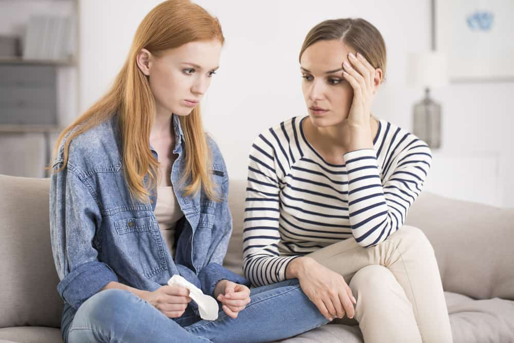 kvinnan tröstar sin vän medan hon sitter på soffan