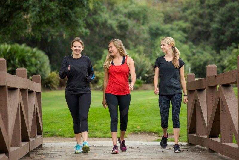 tre kvinnor som går i parken