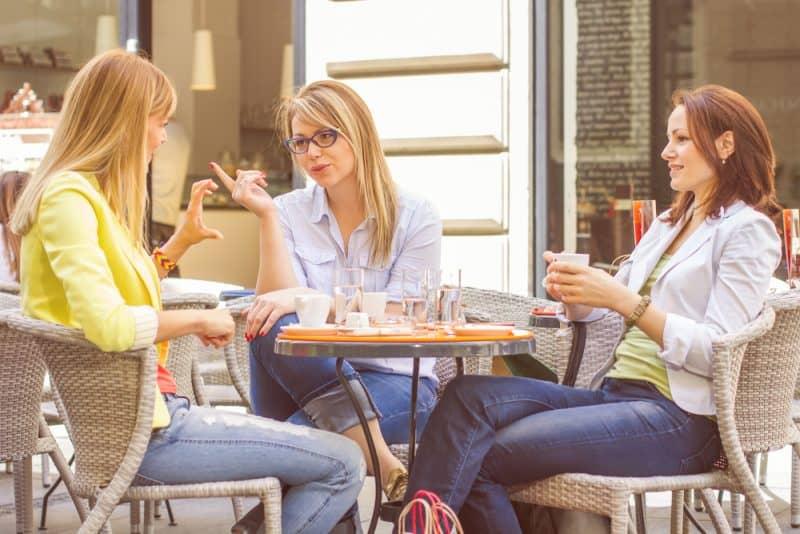 tre kvinnor som sitter vid bordet och pratar och dricker kaffe