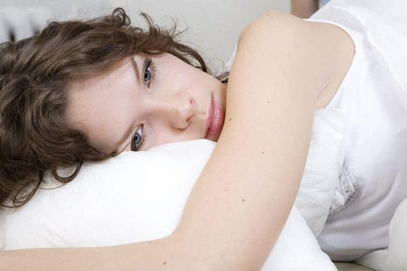ledsen kvinna i djupa tankar i sängen