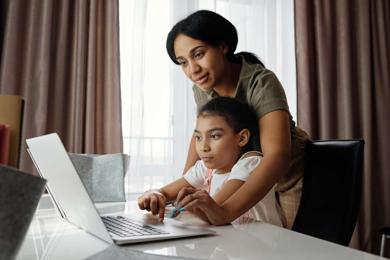 mamma lärande dotter att använda laptop