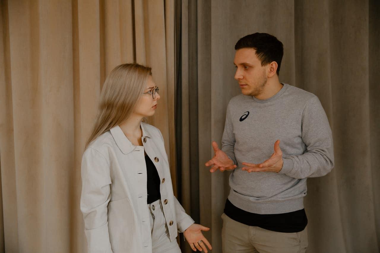 man och blond kvinna med glasögon argumenterar