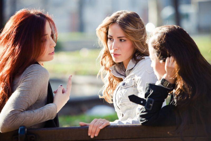 tre kvinnor som sitter i parken och pratar