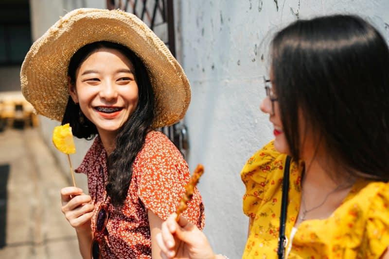 två flickor som står utomhus och ler