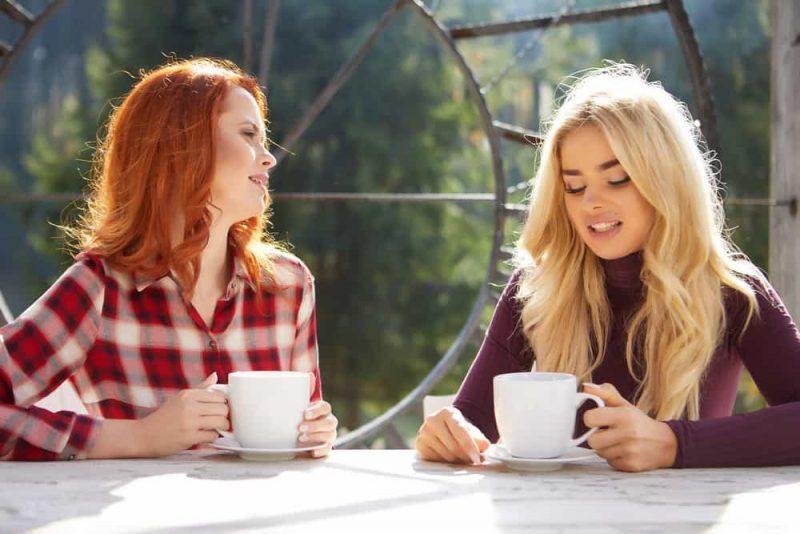 två kvinnor som sitter och dricker kaffe och pratar