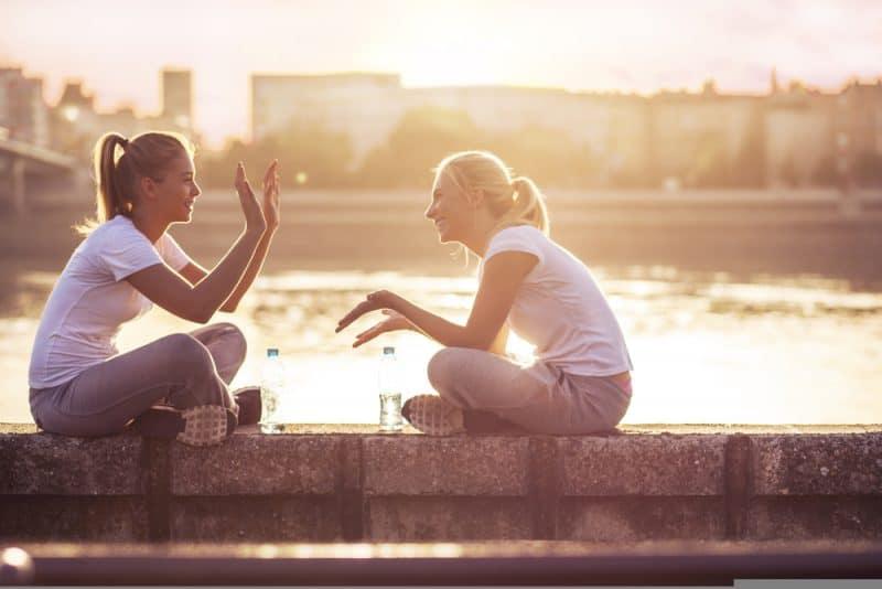två kvinnor som bär vita skjortor som sitter utomhus och pratar