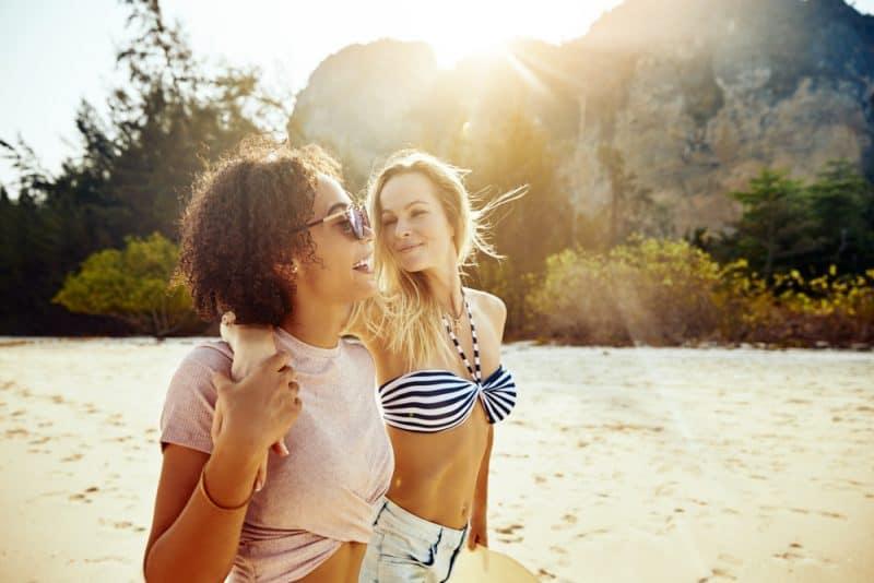 två kvinnor som går på stranden