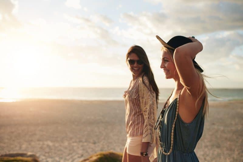 två kvinnor som ler och går på stranden