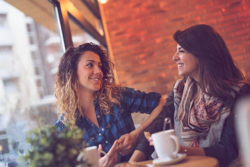 två kvinnor som sitter på café