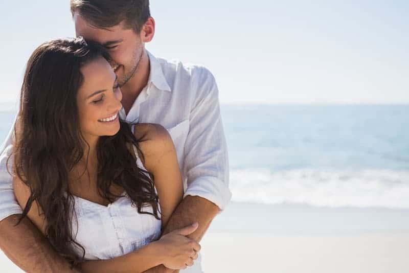ung man kramar kvinna på stranden