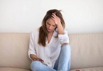 kvinna som sitter på soffan och tittar på telefonen