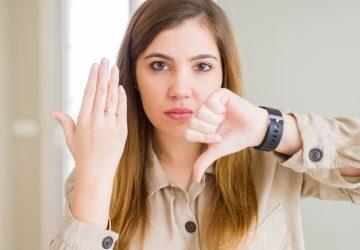 kvinna som pekar med fingret och visar förlovningsringen