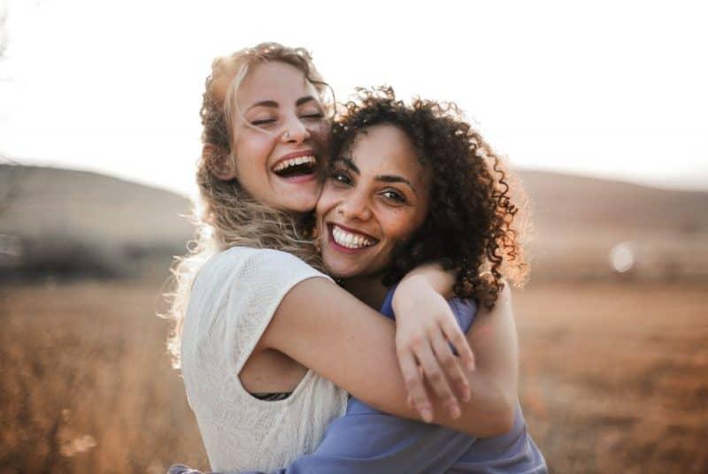 två glada vänner kramar