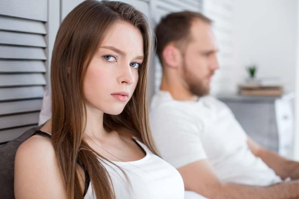 man upprörd med kvinnan som sitter på soffan