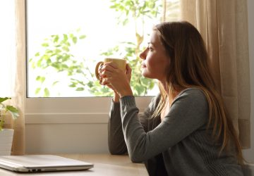 kvinna som håller kopp te som tittar genom fönstret