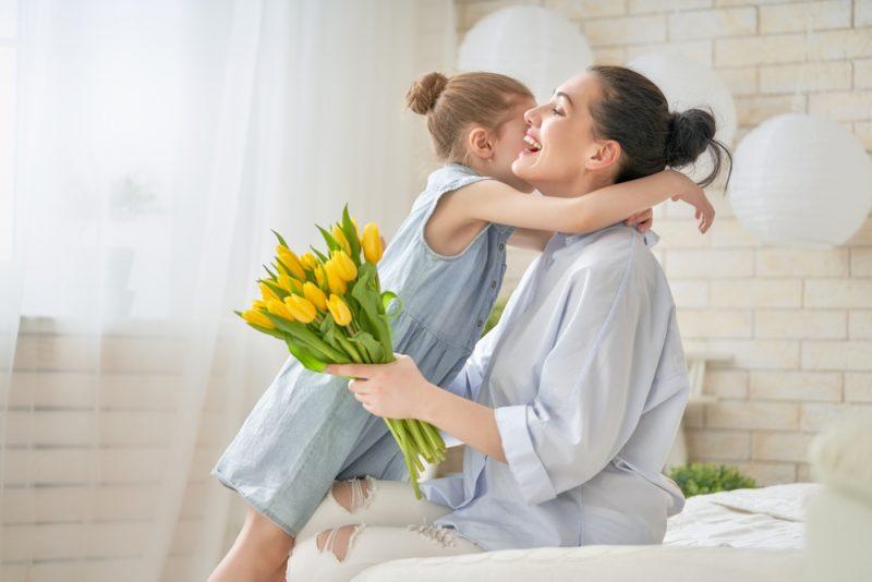 Barnbarn gratulerar mamma och ger henne blommor tulpaner