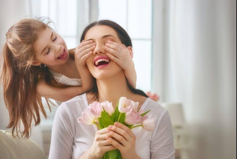 Barndotter gratulerar mamma och ger blommorna tulpaner