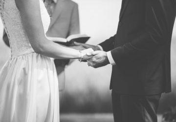 Brud och brudgum som rymmer händer under bröllopceremoni